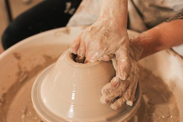 Gros plan de la main de potier créant un pot en terre sur le cercle Photo gratuit