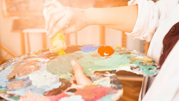 Gros plan, main, presser, jaune, tube peinture, sur, palette peinture Photo gratuit