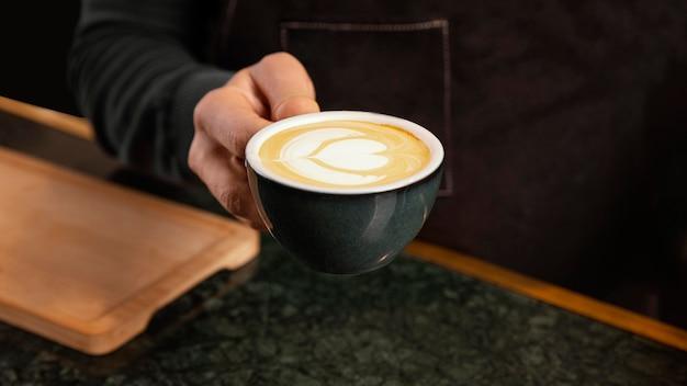 Gros Plan Main Tenant Le Café Avec De La Crème De Lait Photo gratuit