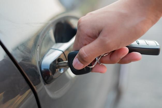 Gros plan une main tenant les clés de la voiture pour déverrouiller ou verrouiller. femme avec la clé de la voiture. Photo Premium