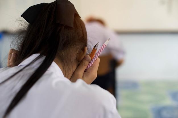 Gros plan d'une main tenant un stylo d'étudiants en uniforme à examiner ou à tester en salle de classe. Photo Premium