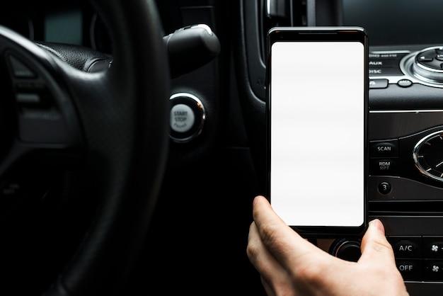 Gros plan, de, a, main, tenant téléphone intelligent, projection, blanc, écran vide, dans voiture Photo gratuit