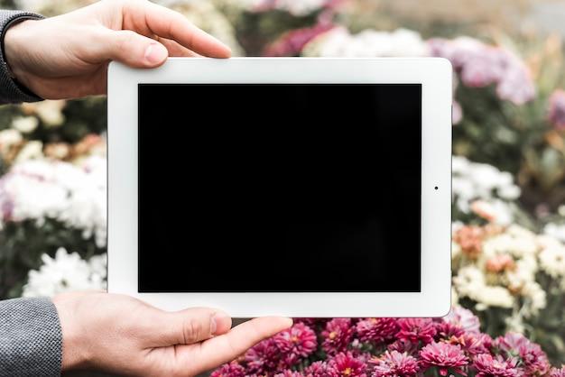 Gros plan, de, main, tenue, tablette numérique, devant, fleurs Photo gratuit