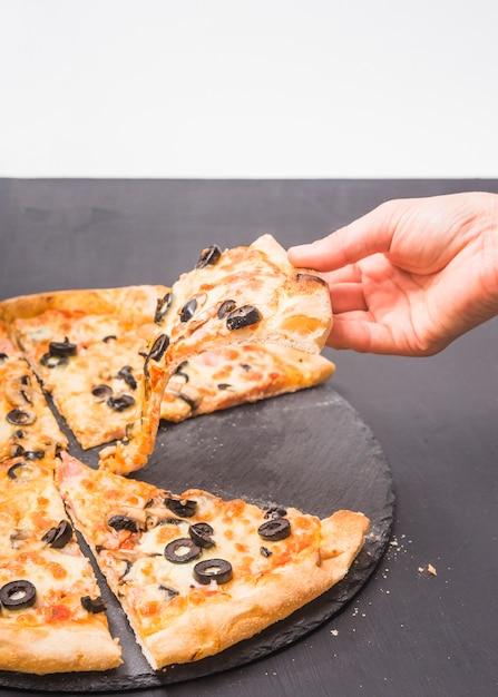 Gros plan, de, main, tenue, tranche pizza, sur, ardoise noire Photo gratuit
