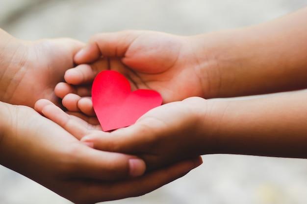 Gros plan des mains adulte et enfant, tenant un coeur rouge. Photo Premium