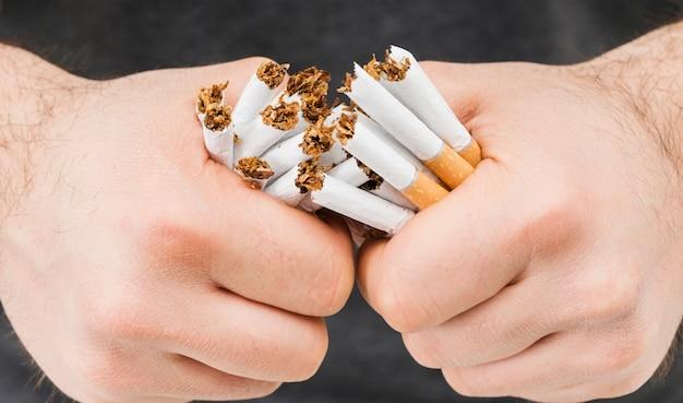 Gros plan, mains, casser, paquet, de, cigarettes Photo gratuit