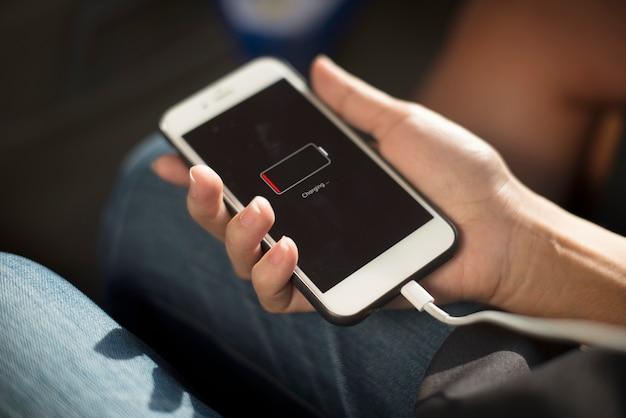 Gros plan des mains chargeant le téléphone portable Photo gratuit