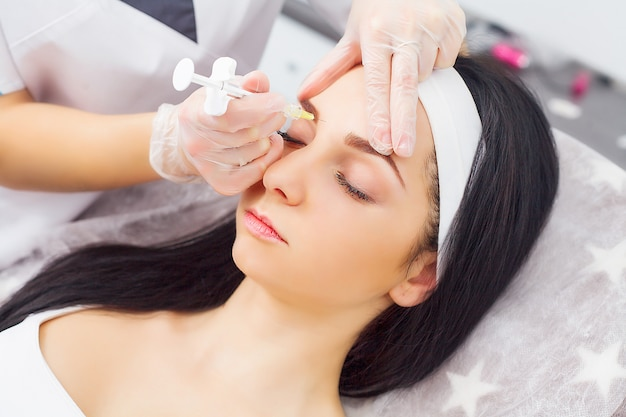 Gros plan des mains de la cosmétologue faisant l'injection de botox dans les lèvres des femmes Photo Premium