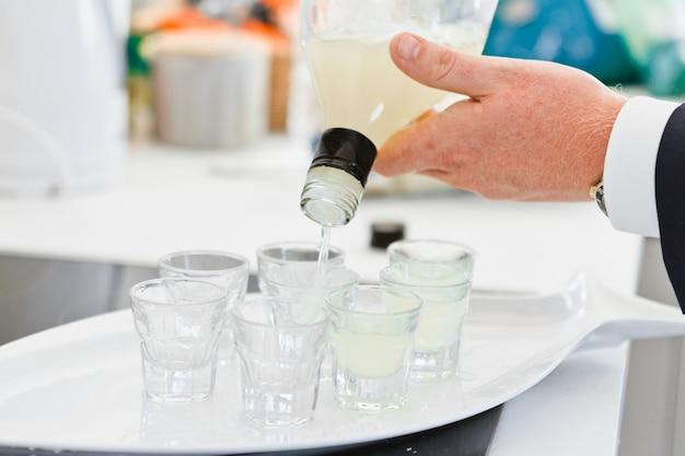 Gros plan des mains du barman verse un verre dans des verres à liqueur Photo Premium