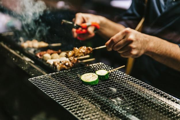 Gros plan des mains du chef japonais yakitori grillant du poulet mariné au gingembre, à l'ail et à la sauce soja et du concombre avec beaucoup de fumée. Photo Premium
