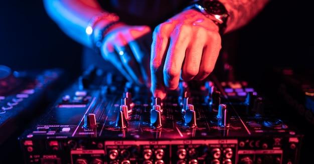 Gros plan des mains du dj contrôlant une table de musique dans une boîte de nuit. Photo Premium