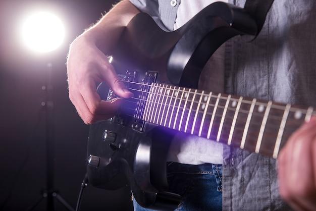 Gros plan des mains du jeune homme joue de la guitare. Photo Premium