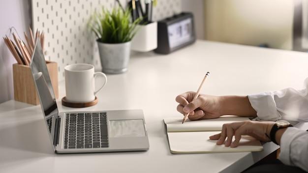Gros plan des mains écrivant sur du papier de cahier Photo Premium