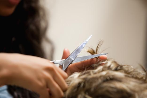 Gros plan des mains féminines coupant les cheveux avec des ciseaux Photo Premium