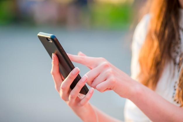 Gros plan des mains féminines tient un téléphone portable à l'extérieur dans la rue en soirée. femme, utilisation, smartphone, mobile Photo Premium