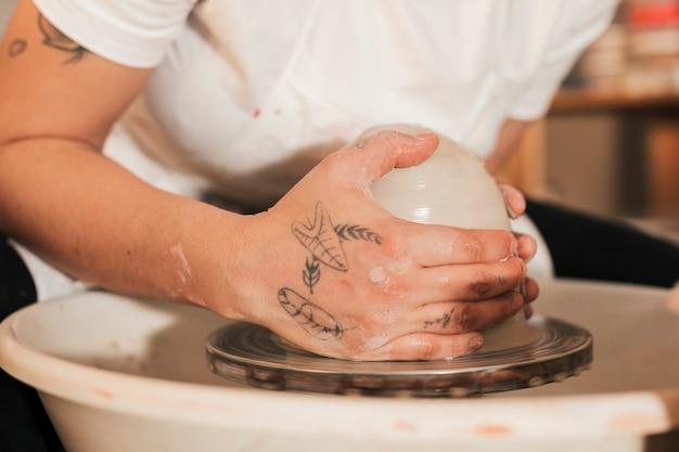 Gros plan des mains de femme potier avec de l'argile sur le tour de potier Photo gratuit