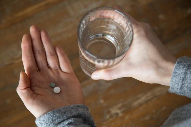 Gros plan des mains de femme tenant un verre d'eau et de pilules Photo gratuit