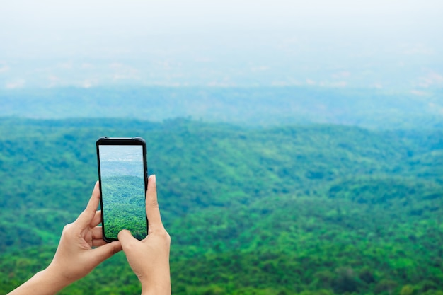 Gros plan des mains de femmes tenant un smartphone prenant une photo à phuhinrongkla à partager sur les médias sociaux internet Photo Premium