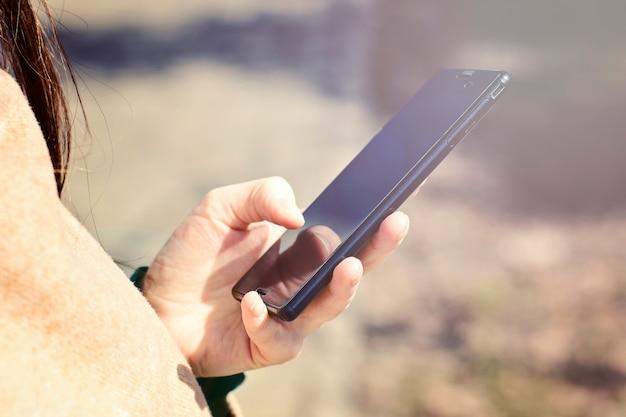 Gros plan des mains de femmes tenant un téléphone cellulaire avec espace copie vierge Photo Premium