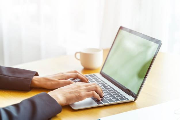 Gros plan des mains de gens d'affaires travaillant avec un ordinateur portable sur la table avec une tasse de café Photo Premium