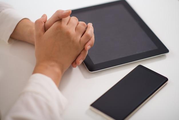 Gros plan, mains jointes, table, pc, tablette, smartphone Photo gratuit