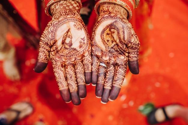Gros plan des mains de la jolie mariée hindoue avec tatouage au henné Photo gratuit
