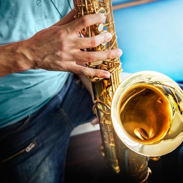 Gros plan des mains jouant du saxophone Photo gratuit
