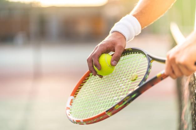 Gros plan des mains de joueur de tennis tenant une raquette avec une balle. Photo Premium