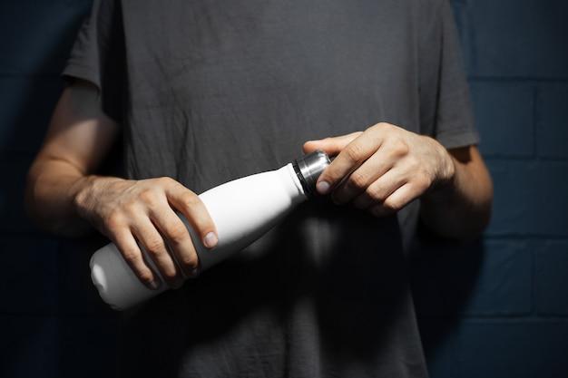 Gros Plan Des Mains Mâles, Ouvre Une Bouteille D'eau Thermo En Acier De Couleur Blanche, Sur Le Fond Du Mur De Briques Noires. Photo Premium