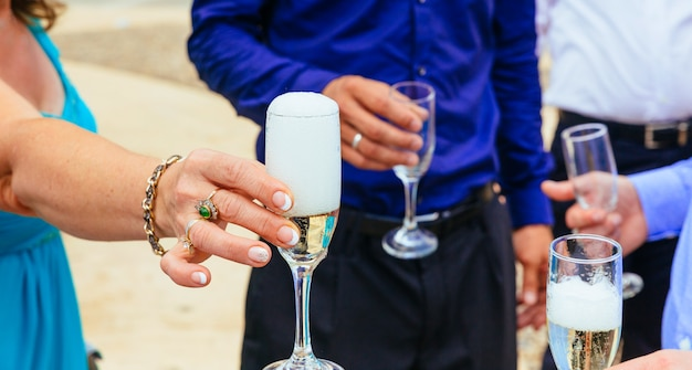 Gros plan des mains des mariés avec des lunettes champagne Photo Premium
