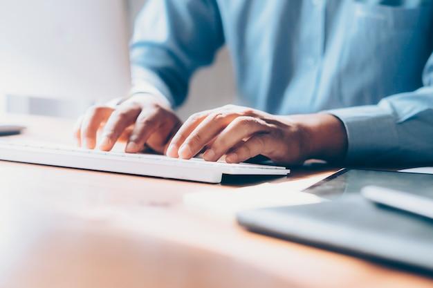 Gros plan des mains masculines à l'aide d'ordinateur. Photo Premium