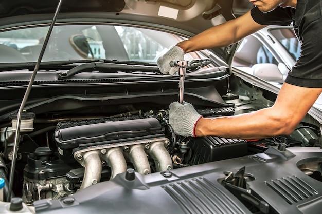 Gros Plan Des Mains De Mécanicien Automobile Utilisent La Clé Pour Réparer Et Entretenir Le Moteur De Voiture Photo Premium