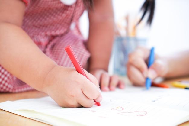 Gros plan des mains d'un petit enfant dessinant au crayon. Photo Premium