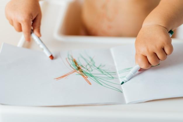 Gros plan des mains d'un petit enfant dessinant avec des marqueurs colorés sur le papier. activité créative Photo Premium