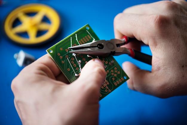 Gros plan des mains avec une pince et une carte mère de circuit informatique Photo Premium