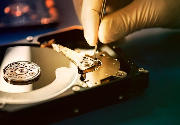 Gros plan des mains avec des pincettes et un disque dur d'ordinateur Photo Premium