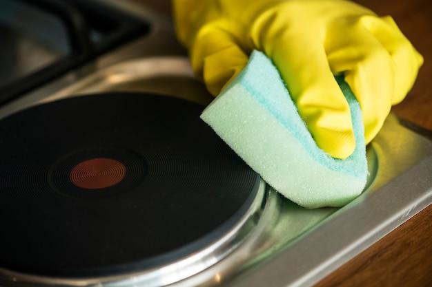 Gros plan des mains portant des gants essuyant le concept de corvées domestiques du poêle Photo gratuit