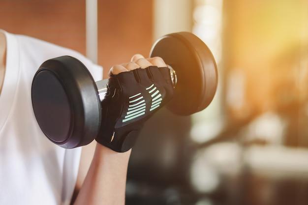 Gros Plan Sur Les Mains Soulevant Des Haltères Dans La Salle De Fitness Photo Premium