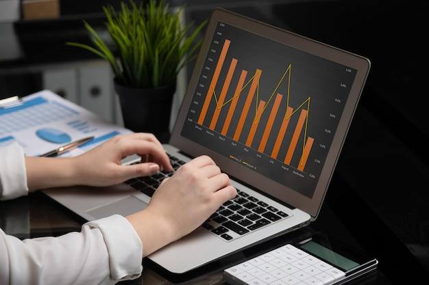 Gros plan des mains en tapant sur un ordinateur portable avec un écran noir vide à côté des graphiques et calculatrice Photo Premium