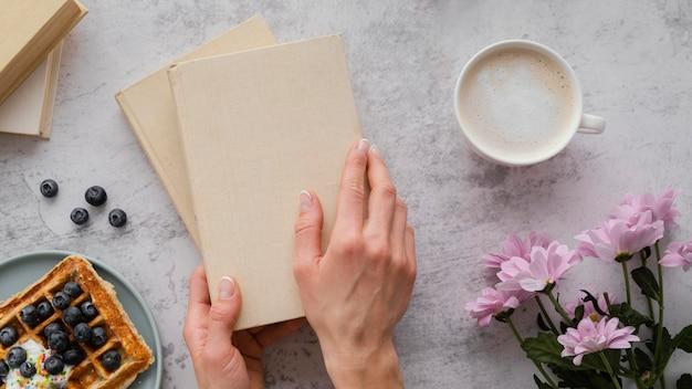 Gros Plan Des Mains Tenant Des Livres Photo gratuit