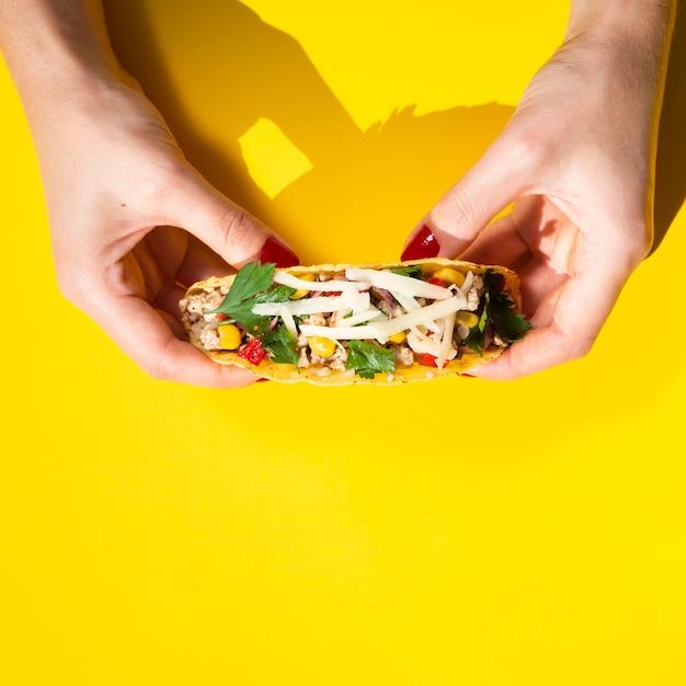 Gros plan, mains, tenue, taco, à, jaune, fond Photo gratuit
