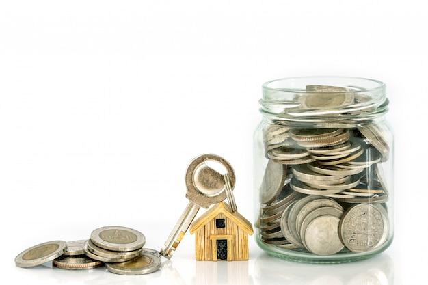 Gros plan de la maison modèle sur l'empilement d'une pièce d'argent pour une hypothèque et un prêt immobilier Photo Premium