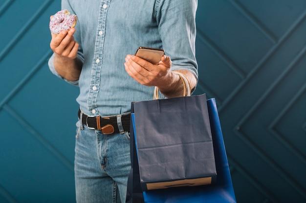 Gros plan, mâle adulte, tenue, sacs provisions Photo gratuit