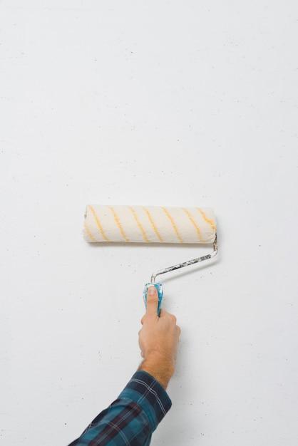 Gros plan, mâle, peintre, peinture, a, mur, à, rouleau peinture, à, espace copie Photo gratuit