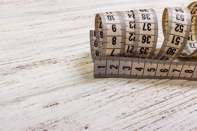 Gros plan sur mesure ruban à mesurer sur fond de table en bois. ruban à mesurer blanc faible profondeur de champ Photo Premium