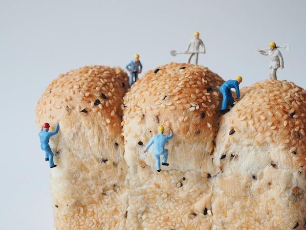Gros plan, miniature, gens, beaucoup, ouvrier, homme, travailler, sur, pain entier, pain, fond Photo Premium