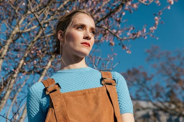 Gros plan modèle féminin sous arbre fleurissant Photo gratuit