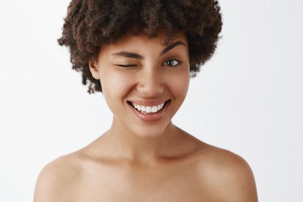 Gros Plan D'un Modèle à La Peau Sombre Attrayant, Joyeux Et Sympathique Avec Une Coiffure Afro Posant Nu, Souriant Largement Et Clignotant Comme S'il Faisait Allusion à Un Concept Intéressant Ou Secret Photo gratuit