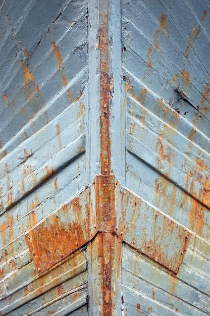 Gros Plan Des Murs De Navire En Fer Rouillé Avec De La Peinture Grise Dessus Photo gratuit
