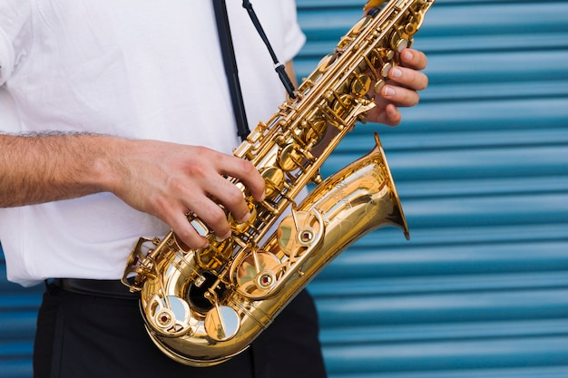 Gros plan musicien tenant saxophone Photo gratuit